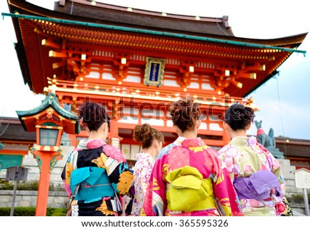 """Young girl wearing Japanese kimono standing in front of japanese Temple in Kyoto, Japan. Kimono is a Japanese traditional garment. The word """"kimono"""", which actually means a """"thing to wear"""" - stock photo"""