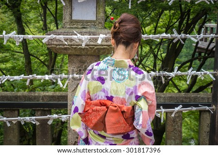 Young girl wearing Japanese kimono with fortune papers - stock photo