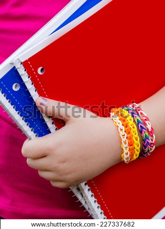 Young girl wearing loom bracelets, Young fashion, outdoors, friendship, crafts, and lifestyle concept. Bright tones. Shallow depth of field.  - stock photo