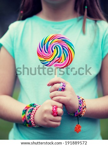 Young girl wearing loom rings and bracelets on her hands. Close up. Young fashion concept. cross processed - stock photo
