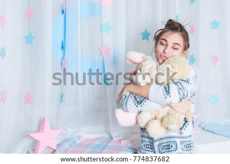 Young Girl Wearing Pajamas In Bed With Cuddly Toy. Cute Teenage Girl Rest  At Home