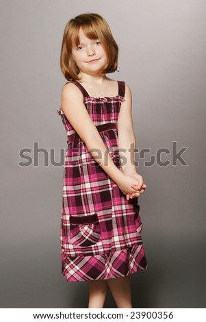 Young girl wearing plaid dress - stock photo