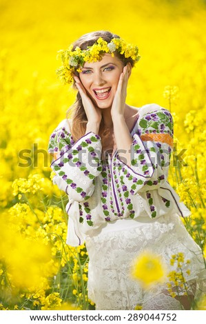 Young girl wearing Romanian traditional blouse posing in canola field, outdoor shot. Portrait of beautiful blonde with flowers wreath smiling in rapeseed field - stock photo