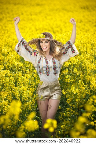Young girl wearing Romanian traditional blouse posing in canola field with cloudy sky in background, outdoor shot. Portrait of beautiful blonde with straw hat smiling in rapeseed field - stock photo