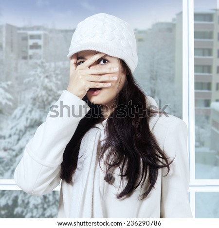 Young girl wearing winter clothes and peeking at the camera through her fingers near the window - stock photo