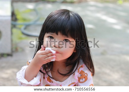 Young girl wiping her mouth after a satisfying meal