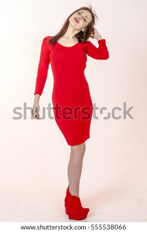 Young girl with a beautiful figure in a trendy red  dress in skin-tight miniskirt and red high heels and platform dressed for a party