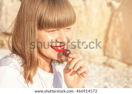 Young girl with a bob hairstyle and red lipstick eating a cherry