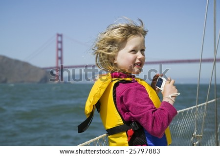 Young girl with a camera on a sailboat near the Golden Gate Bridge - stock photo