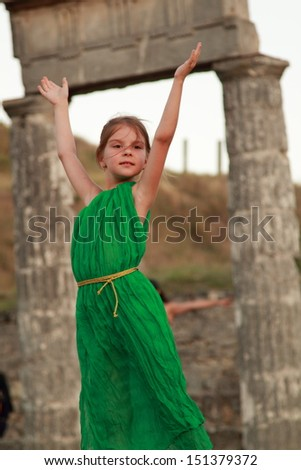 Young girl with a charming smile in vintage dress on a background of the excavation of ancient Greek city - stock photo