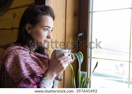 Young girl with a cup of coffee standing at the window