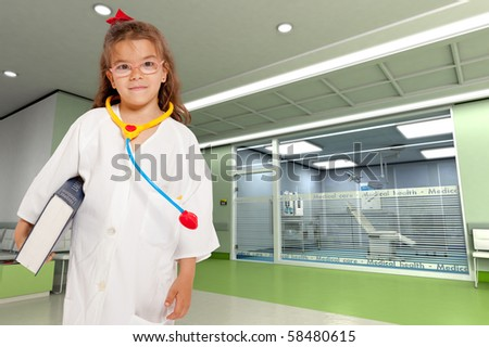 Young girl with a doctor?s uniform and toy stethoscope holding a book in a hospital interior - stock photo