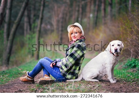 Young girl with a dog in the wood - stock photo