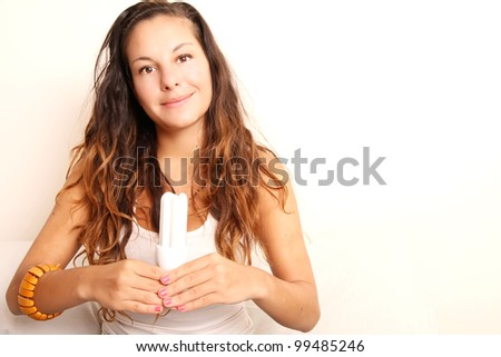 Young girl with a energy saver light bulb. - stock photo