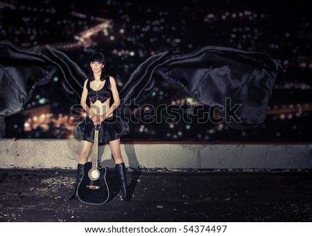 young girl with a guitar on a roof of a high-rise building