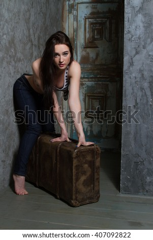 Young girl with a huge old suitcase
