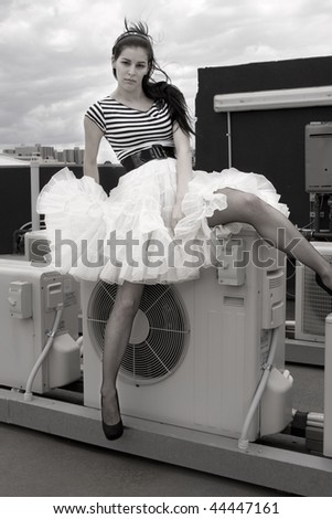 Young girl with a ruffle skirt sitting on an air conditioning unit