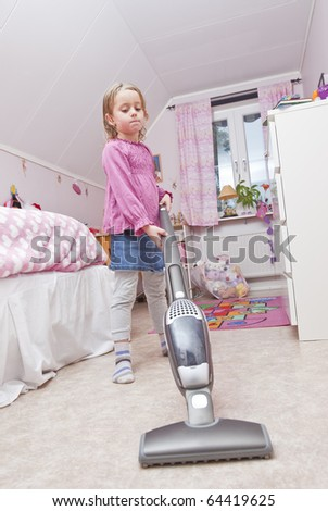 Young Girl with a vacuum cleaner in her room - stock photo
