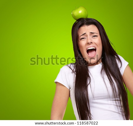 Young Girl With Apple On Head Isolated On Green Background