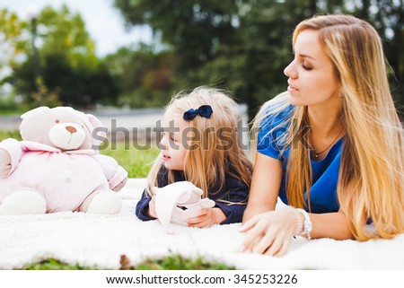 Young girl with beautiful mom resting in park. Both blonds and wear blue dresses. Girl playing with toys. Picnic outdoors on warm summer day. Copy space - stock photo