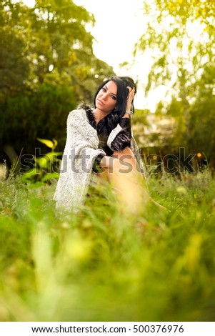 Young girl with black hair sitting on the grass in the park