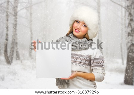 Young girl with blank poster on snowy forest background - stock photo