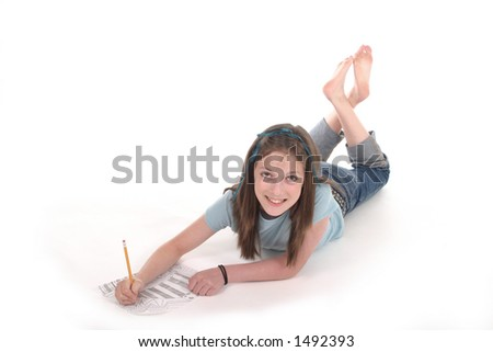 Young girl with blue ribbon in her hair drawing and scribbling on paper on the floor.