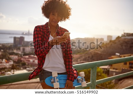 Young girl with blue skateboard and cell phone wearing denim shorts, a white tank top and red and black shirt, looking at the camera
