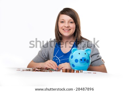 young girl with blue spotted piggy bank counting money isolated on white background - stock photo