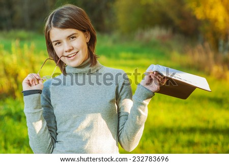 Young girl with book and glasses has reflected against an autumn field. - stock photo