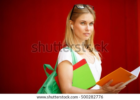 Young girl with book in headphones on empty Brown background