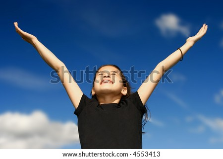Young girl with both arms wide open, facing the bright sunshine against deep blue sky in the background, celebrating beauty of nature. - stock photo
