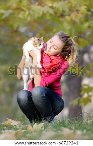young girl with cat on natural background - stock photo