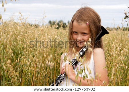 Young girl with clarinet at cornfield