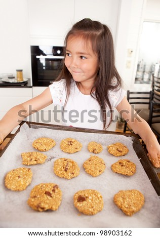 Young girl with cookie sheet filled with raw cookies - stock photo