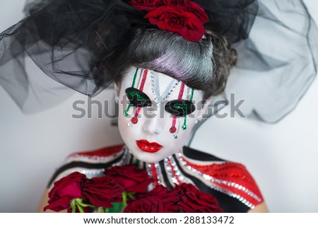 Young girl with creative body painting holding bouquet of red roses. Black Veil, silver hair design. The woman is a carnival character with colorful shiny stripes on face and shoulders. Halloween art - stock photo
