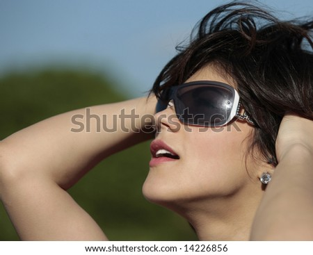 young girl with dark glasses looking at the sky