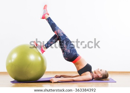 Young girl with dark hair wearing pink snickers, dark leggings and black short top doing exercises with fitball at gym, fitness, mats, copy space. - stock photo