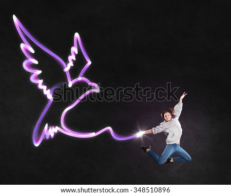 Young girl with drawn wings jumping high in sky