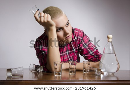 Young girl with drinking problem sitting by table surrounded with Alcohol bottle and shoots