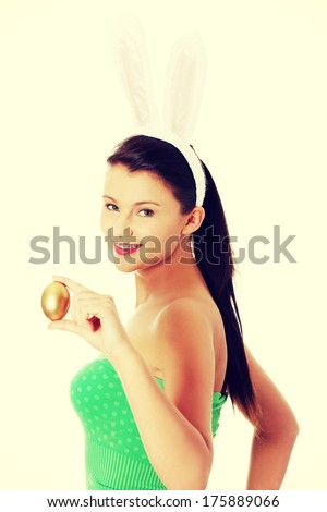 Young girl with easter bunny ears holding golden egg
