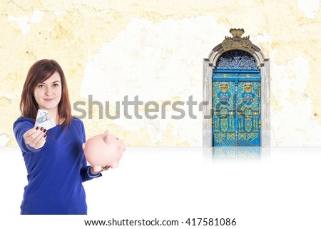 Young girl with euro ticket on hand holding a piggy bank - stock photo