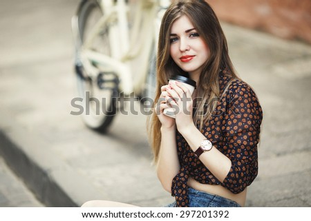 Young girl with fair hair wearing on short dark blouse is posing with coffee on tiled pavement with bicycle on a background on the street of old city  - stock photo