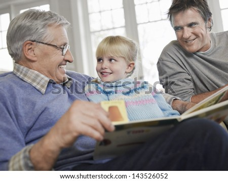 Young girl with father and grandfather reading story book at home - stock photo