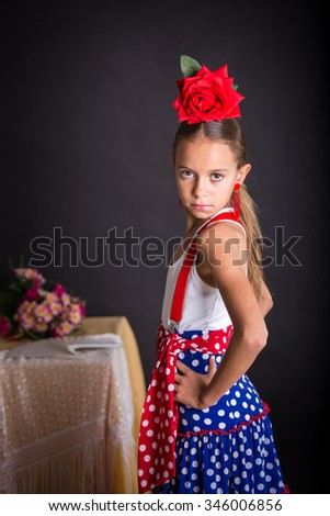Young girl with flamenco outfit and sober look on black background - stock photo