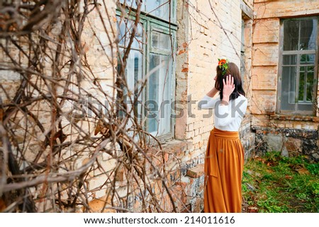 Young girl with flower wreath on her head looking out the wooden window of an old brick building with branches in the foreground - stock photo