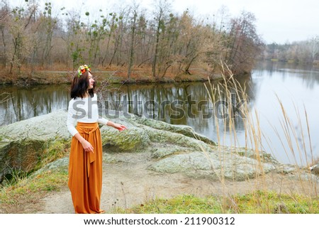 Young girl with flower wreath outdoors near the river