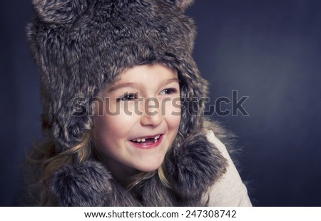 Young girl with fur winter hat, laughing and looking to the side - stock photo