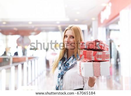 Young girl with gift boxes in the store. character of shopping