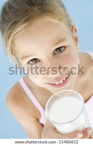 Young girl with glass of milk smiling - stock photo